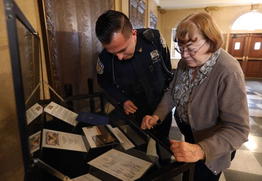 City Clerk Anne McPherson shows  police officer Juan Santa memorabilia from the World War I exhibit at White Plains City Hall Nov. 8, 2018.