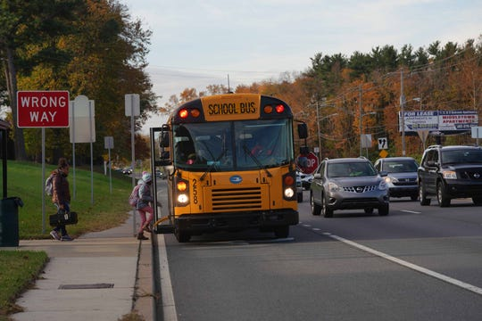 Children board a school bus near Galloway Court Apartments on U.S. 13 on Thursday morning as traffic heeds the stop sign deployed from the school bus.