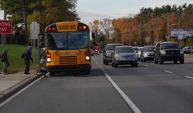 Children board a school bus near Galloway Court Apartments on Route 13 Thursday morning as traffic heeds the STOP arm deployed by the driver.