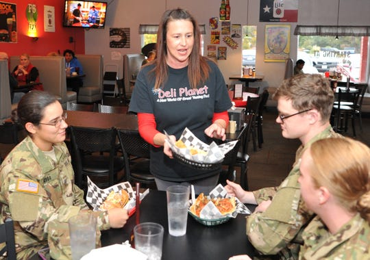 In this photo from 2018, Deli Planet Owner/Operator Rebecca Rutledge serves food to a table of Sheppard Air Force Base airmen. The restaurant will be doing his fifth annual free buffet for military members on Thanksgiving Day. They will also serve pizza at 5 p.m. and stay open until 8 p.m. for people to enjoy a few drinks or watch the football games.