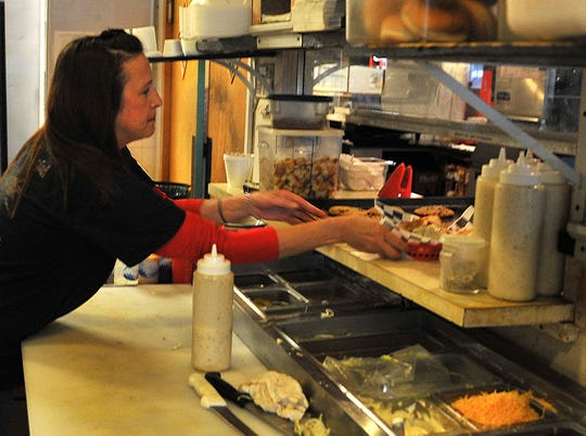 Deli Planet owner/operator Rebecca Rutledge prepares an order Thursday afternoon.