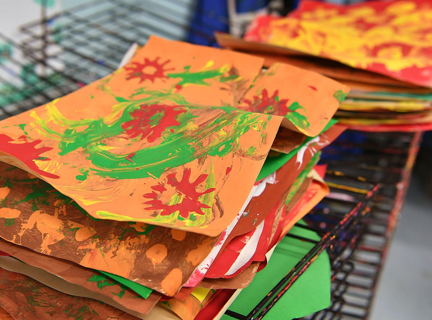 Artwork using tempera paints on paper are stacked on a drying rack in Audra Miller's art classroom at Fain Elementary.