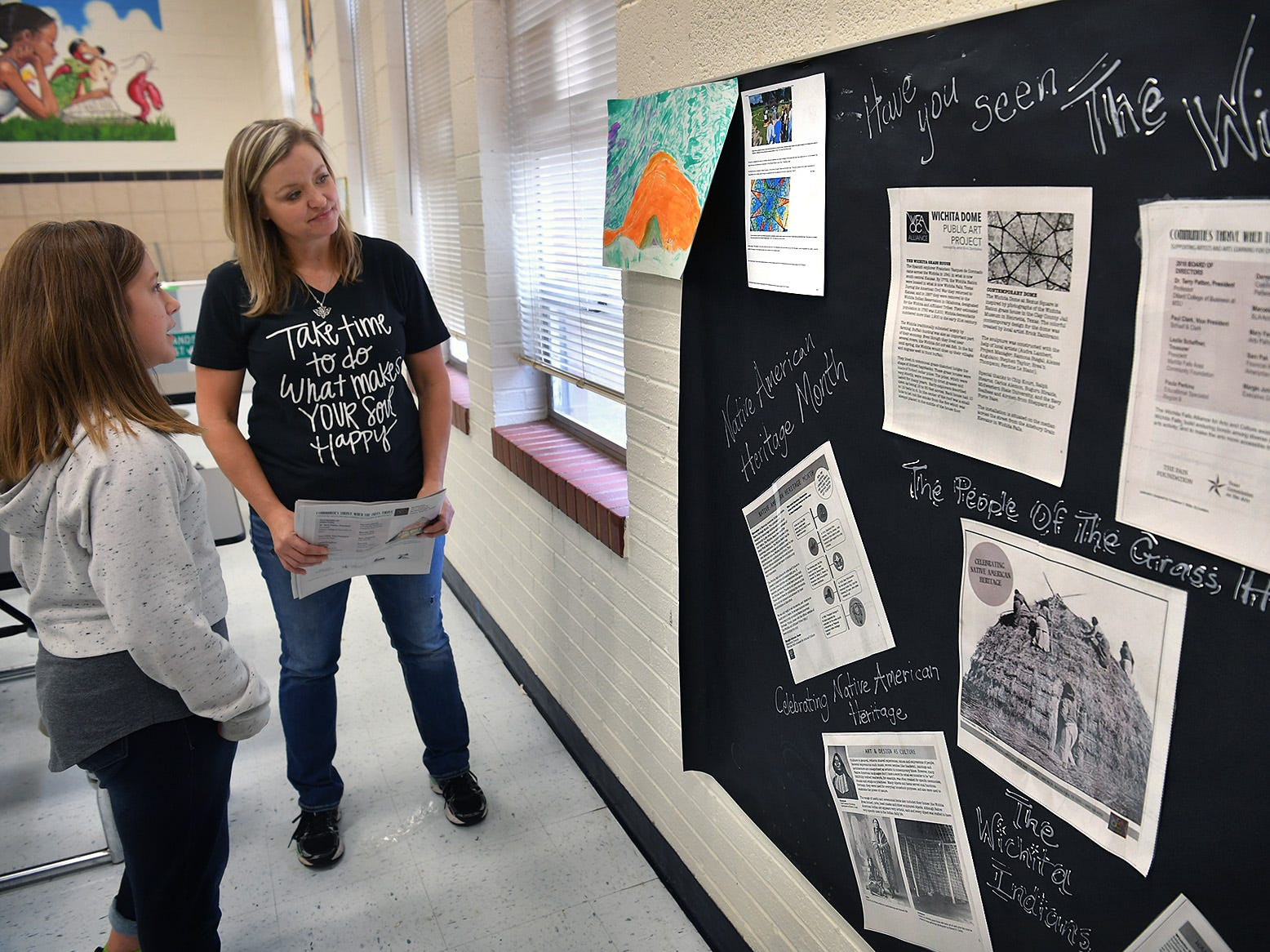 Fain Elementary art teacher Audra Miller talks with her student, Emma Schreiber, about the artwork she created while working on the assignment to celebrate National Native American Heritage Month.