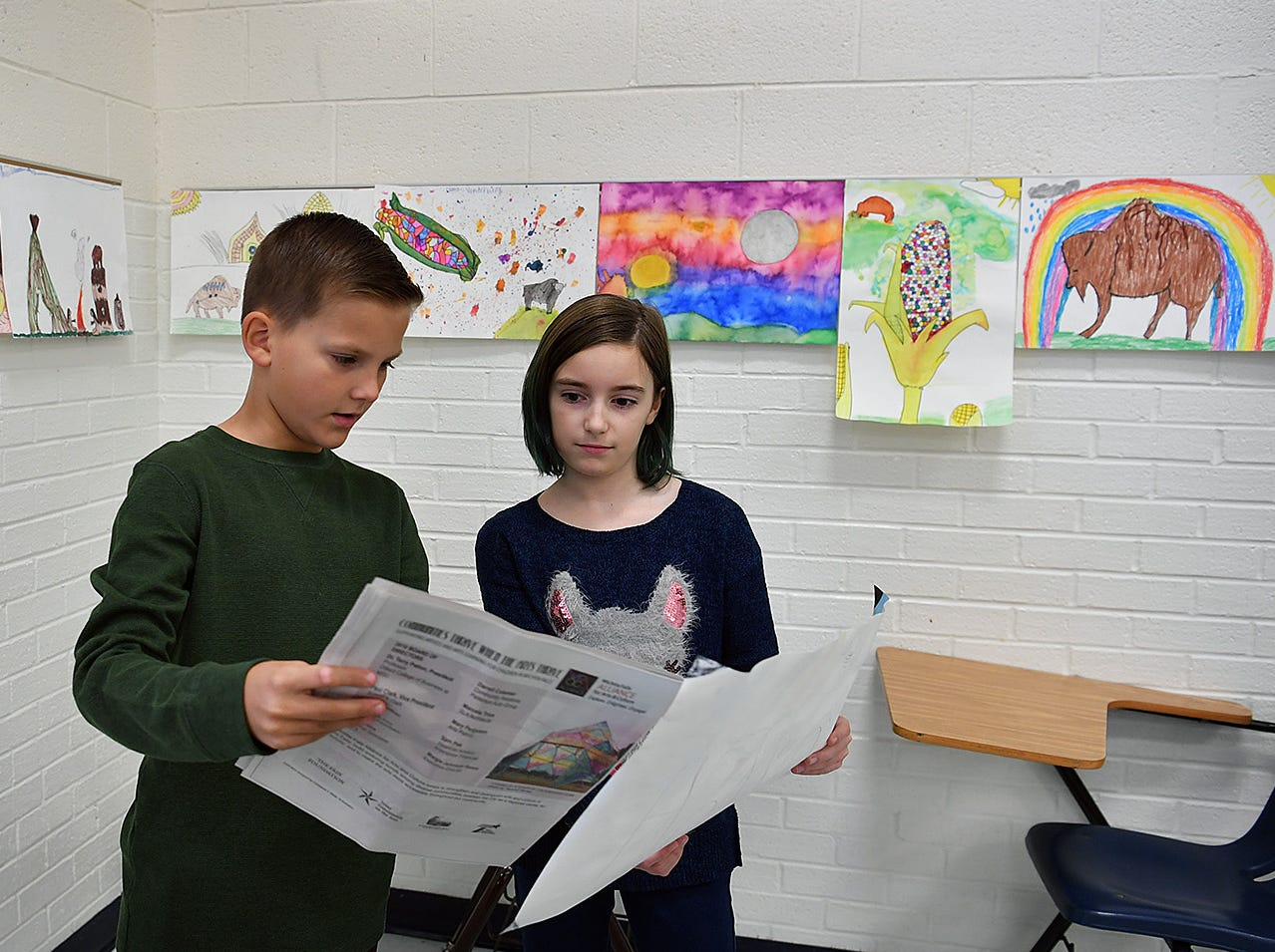 Graham Archer and Hollin Chandler look at a publication created with the Times Record News and the Wichita Falls Alliance for Arts and Culture that focuses on National Native American Heritage and an art project at Fain Elementary.