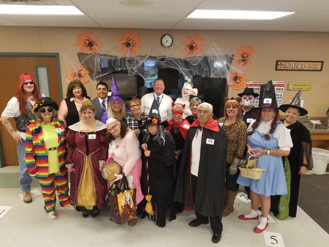 Fall Festival 2018 at the Red Door on Oct. 31, was a haunting success!  Celebrity judges Mayor Stephen Santellana, KAUZ's Chris Horgen, KFDX's Darrell Franklin, and Senior Junior Forum President Debbie Berend chose Best Costume this year.  The winners were: 2nd place Becky Skacilas dressed as a Mummy with her child, and 1st place was Kay Green as Naughty Dorothy with Toto her dog.  The day also consist of a cake walk, plinko, duck game, and a dice game.  The staff handed out candy down their decorated hallway.  Pictured left to right: front rows – Cookie Pruett, Pauletta Perez, Cheryl Dye, Connie Perez, Delores Casa, Pat Reu, Ann Renick, Glenda Arrendondo, Oscar Arrendondo, Patricia Lamb, Salvador Melesio, Kay Green, and Maria Melesio Back row – Darrell Franklin, Debbie Berend, Stephen Santellana, Chris Horgen, and Becky Skacilas