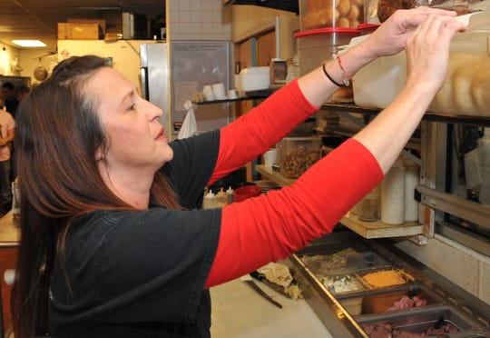 Deli Planet owner/operator Rebecca Rutledge prepares an order Thursday afternoon. Going on their fourth year, the restaurant offers a free Thanksgiving-style meal to airmen on the holiday. Last year they hosted more than 200 airmen and ran out of food. This year she said they will have plenty of food and expect even more visitors.