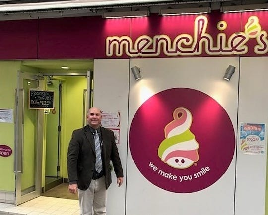 California dairy farmer Brad Scott smiles in front of a Menchie's frozen yogurt store in Tokyo this week knowing milk from his cows helps make a tasty treat in Asia and around the world.