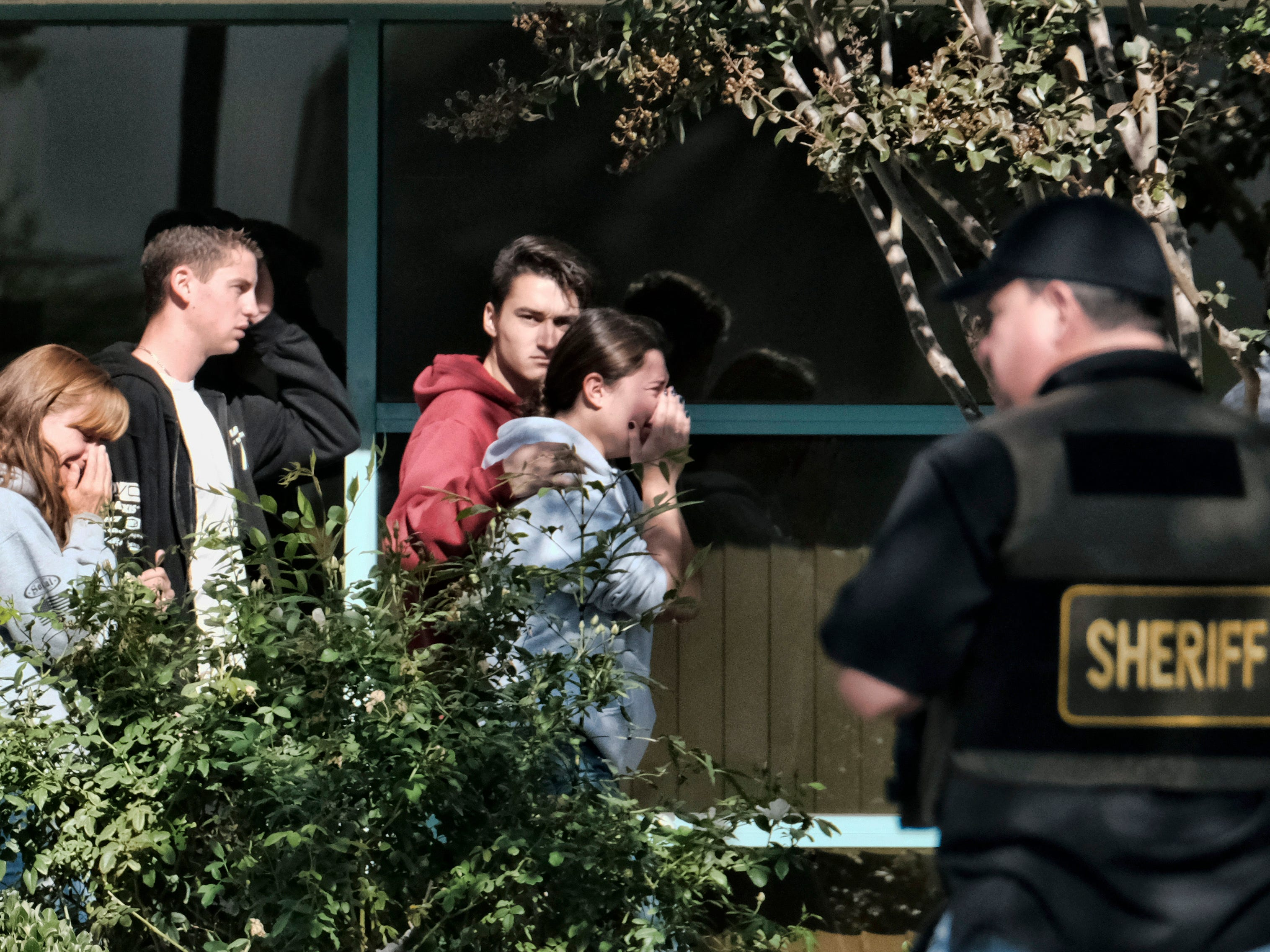 Grieving people are led into the Thousand Oaks Teen Center where families have gathered after a deadly shooting at a bar on Thursday, Nov. 8, 2018, in Thousand Oaks, Calif. Multiple people were shot and killed late Wednesday by the gunman who opened fire at the Borderline Bar & Grill, which was holding a weekly country music dance night for college students.