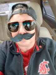 Washington State graduate Jennie Dickinson is among those sporting fake mustaches and sunglasses as the Gardner Minshew craze sweeps Pullman, Wash.