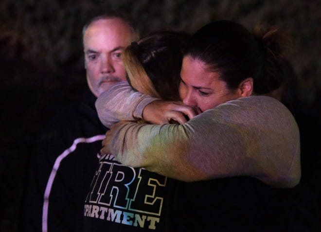 A woman who fled the Borderline Bar & Grill where a gunman injured 11 people is hugged by relatives in Thousand Oaks, California.