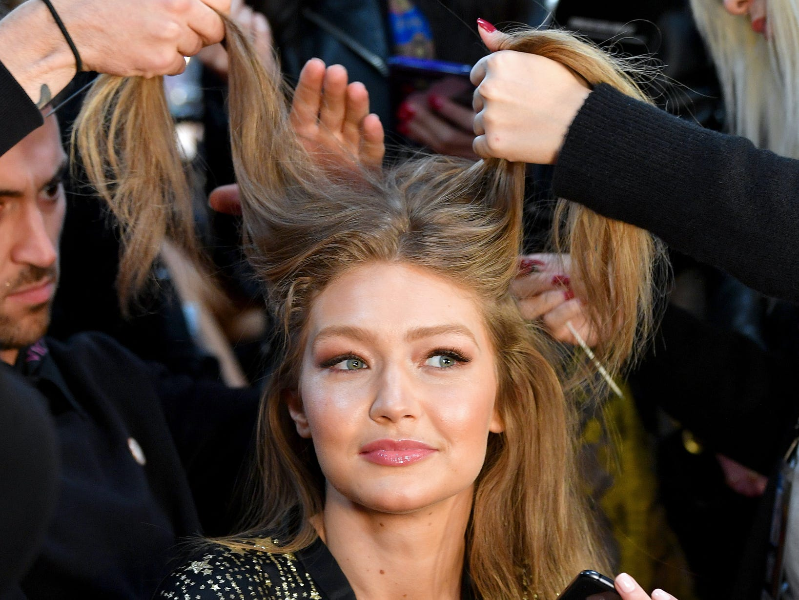 Gigi Hadid gets hair care backstage.
