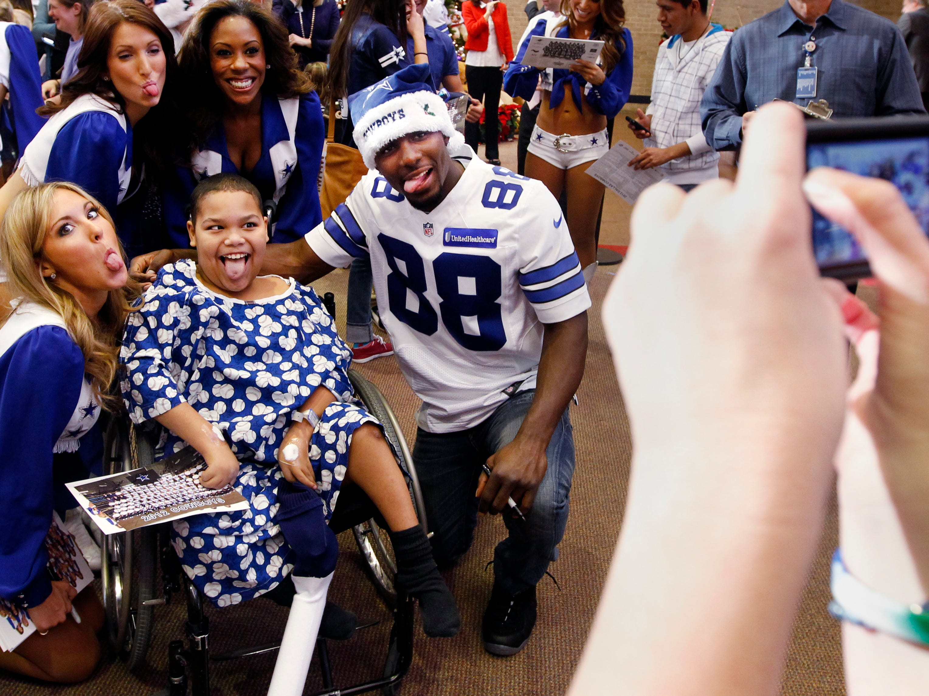 Myron Miller, 11, of Fort Worth makes a funny face while posing with Dez Bryant and Dallas Cowboys cheerleaders during their annual visit at the Texas Scottish Rite Hospital for Children in 2012.