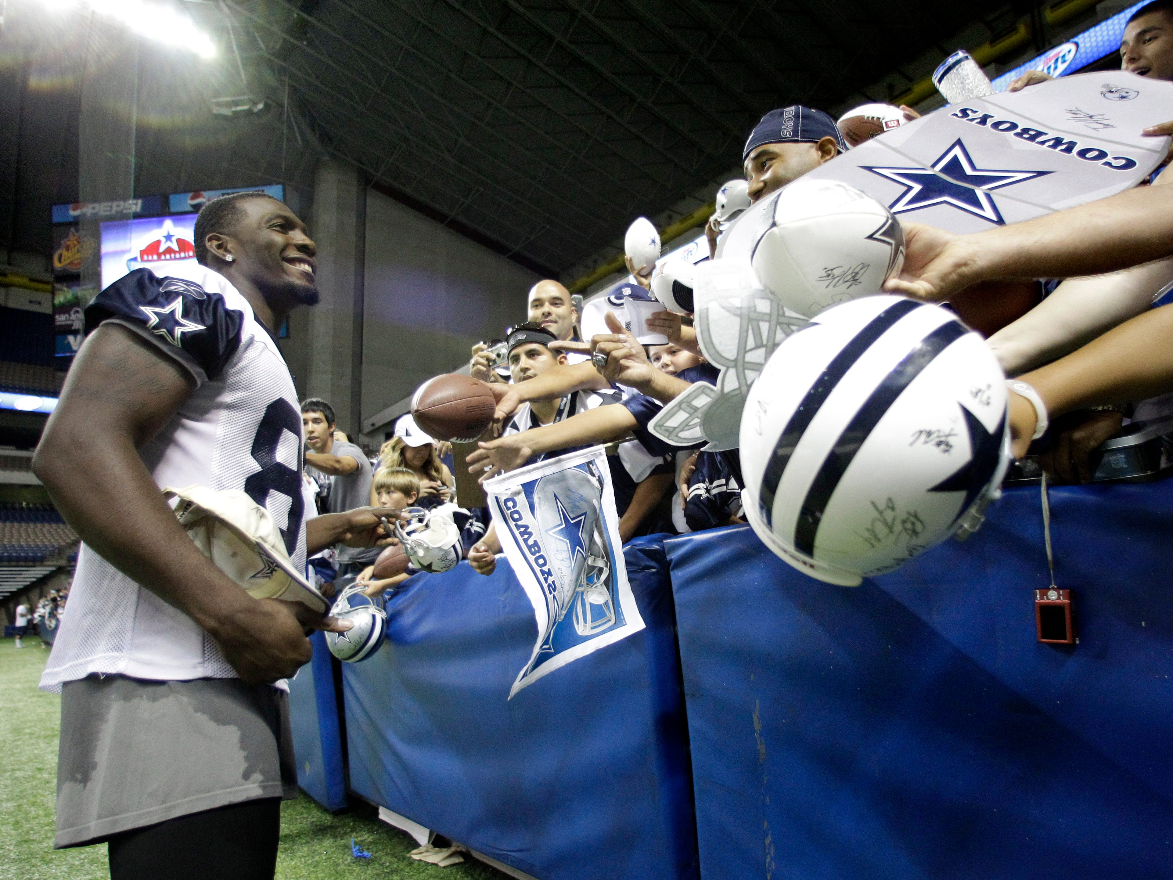 Dez Bryant smiles as he poses for a photograph by a fan as others ask for autographs following a practice on the opening day of Cowboys training camp  in San Antonio in 2010.