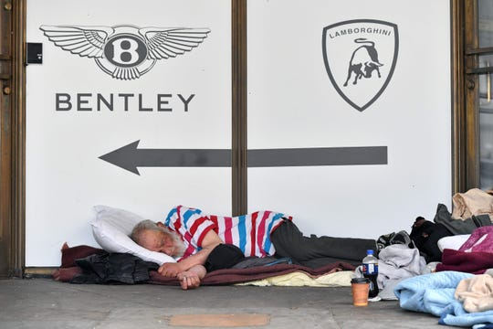 In this file photo taken on June 09, 2016, a homeless man sleeps in front of a luxury auto dealership in San Francisco, California.