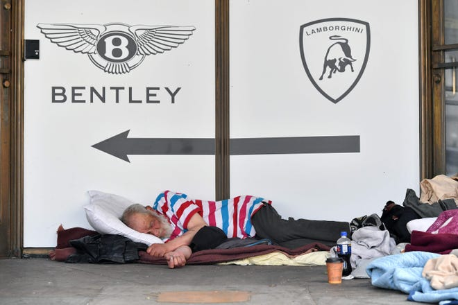 In this file photo taken on June 09, 2016 A homeless man sleeps in front of a luxury auto dealership in San Francisco, California.