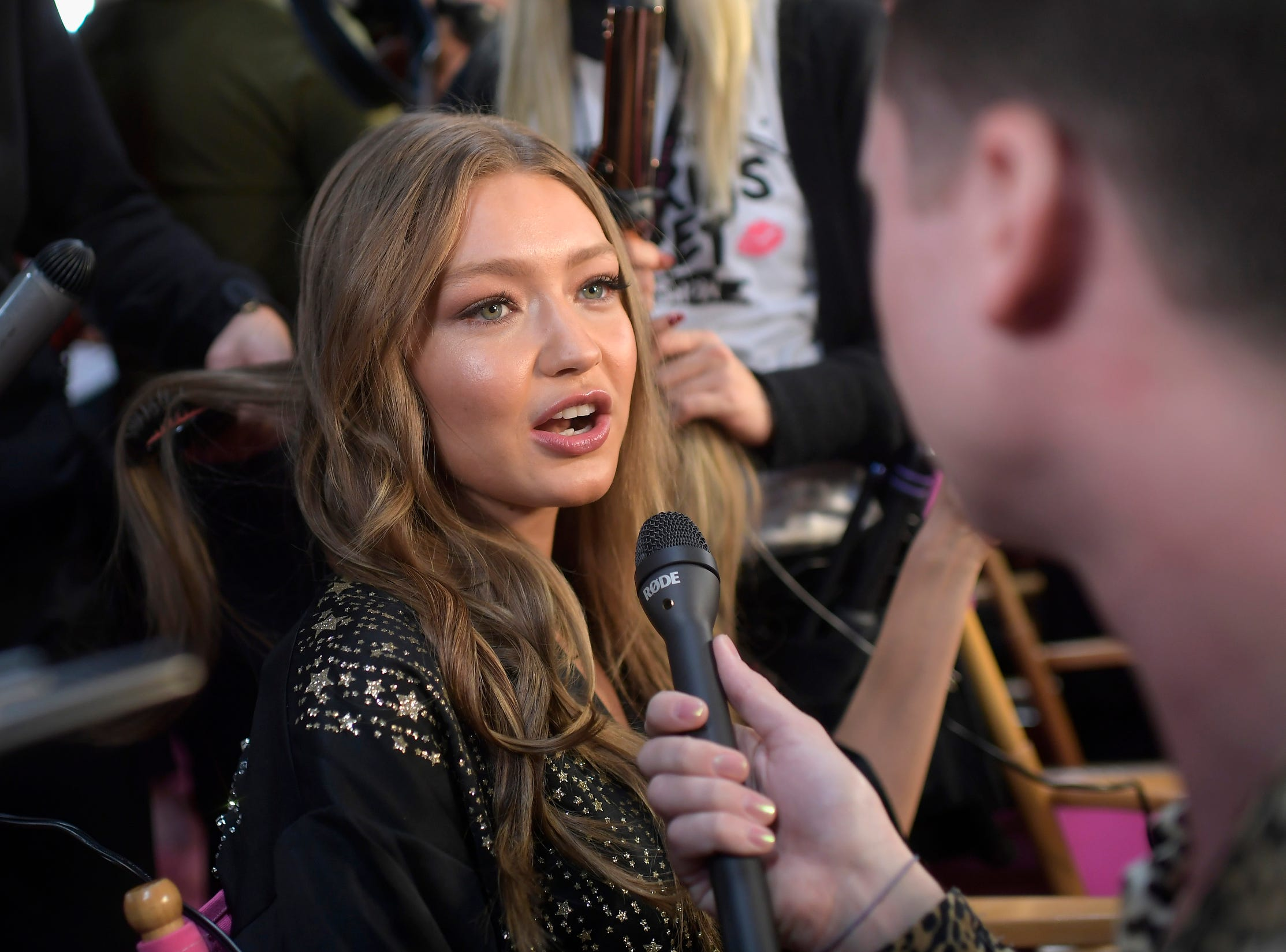 Gigi Hadid takes media questions backstage.