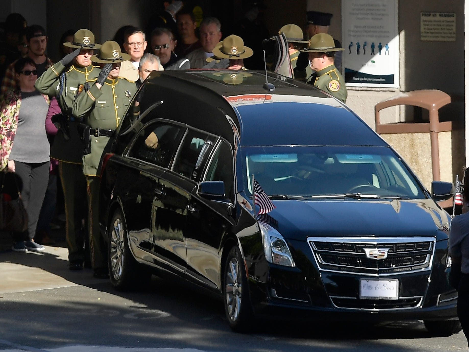 """An honor guard salutes the body of Ventura County Sheriff's Department Sgt. Ron Helus before it departs the Los Robles Regional Medical Center Thursday, Nov. 8, 2018, in Thousand Oaks, Calif. Helus was killed after a gunman opened fire the night before inside a country dance bar crowded with hundreds of people on """"college night."""""""