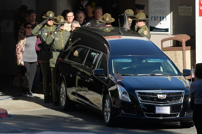 "An honor guard salutes the body of Ventura County Sheriff's Department Sgt. Ron Helus before it departs the Los Robles Regional Medical Center Thursday, Nov. 8, 2018, in Thousand Oaks, Calif. Helus was killed after a gunman opened fire the night before inside a country dance bar crowded with hundreds of people on ""college night."""