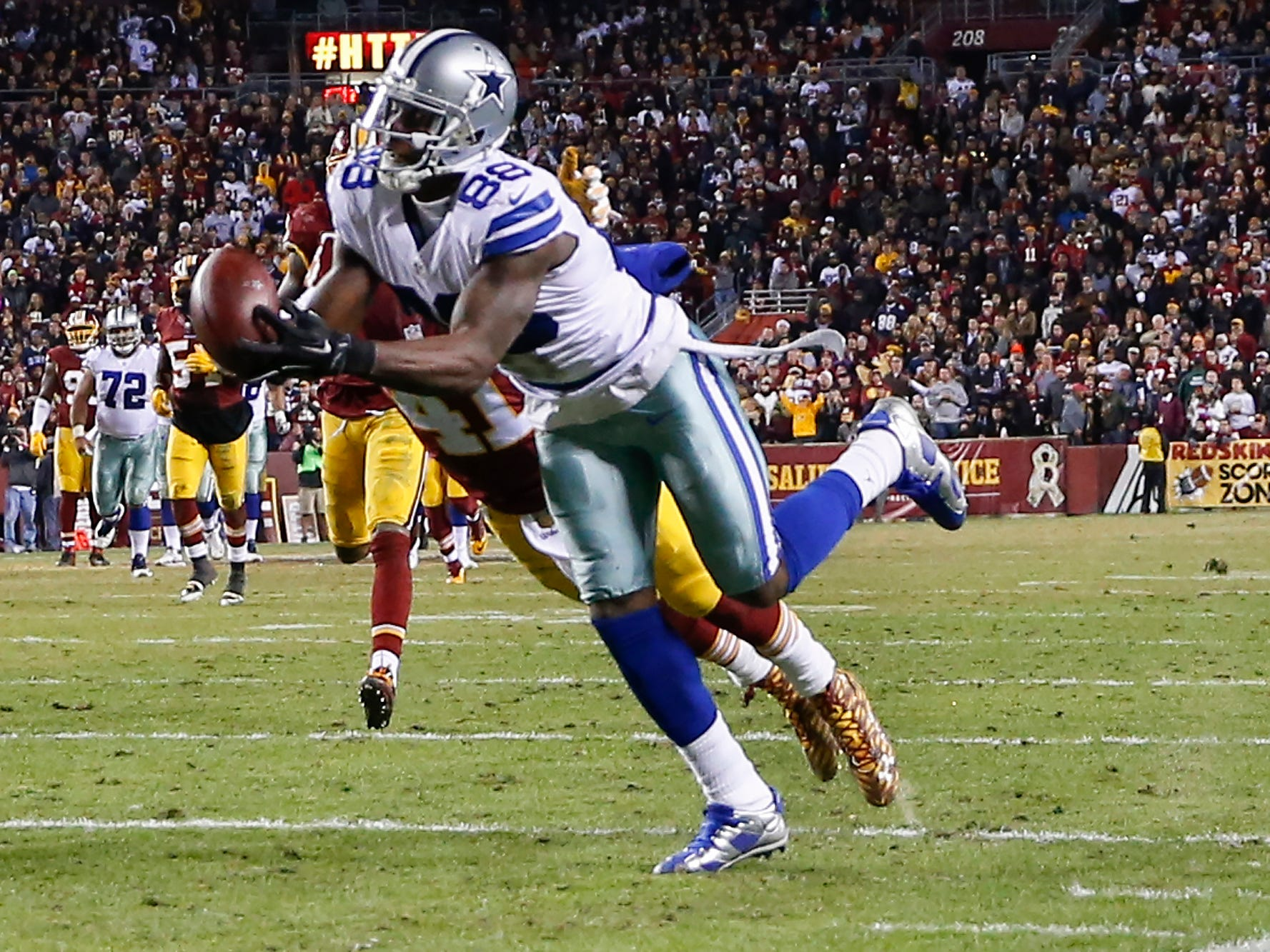 Dez Bryant pulls in a pass under pressure from Washington Redskins cornerback Will Blackmon during a game in 2015.