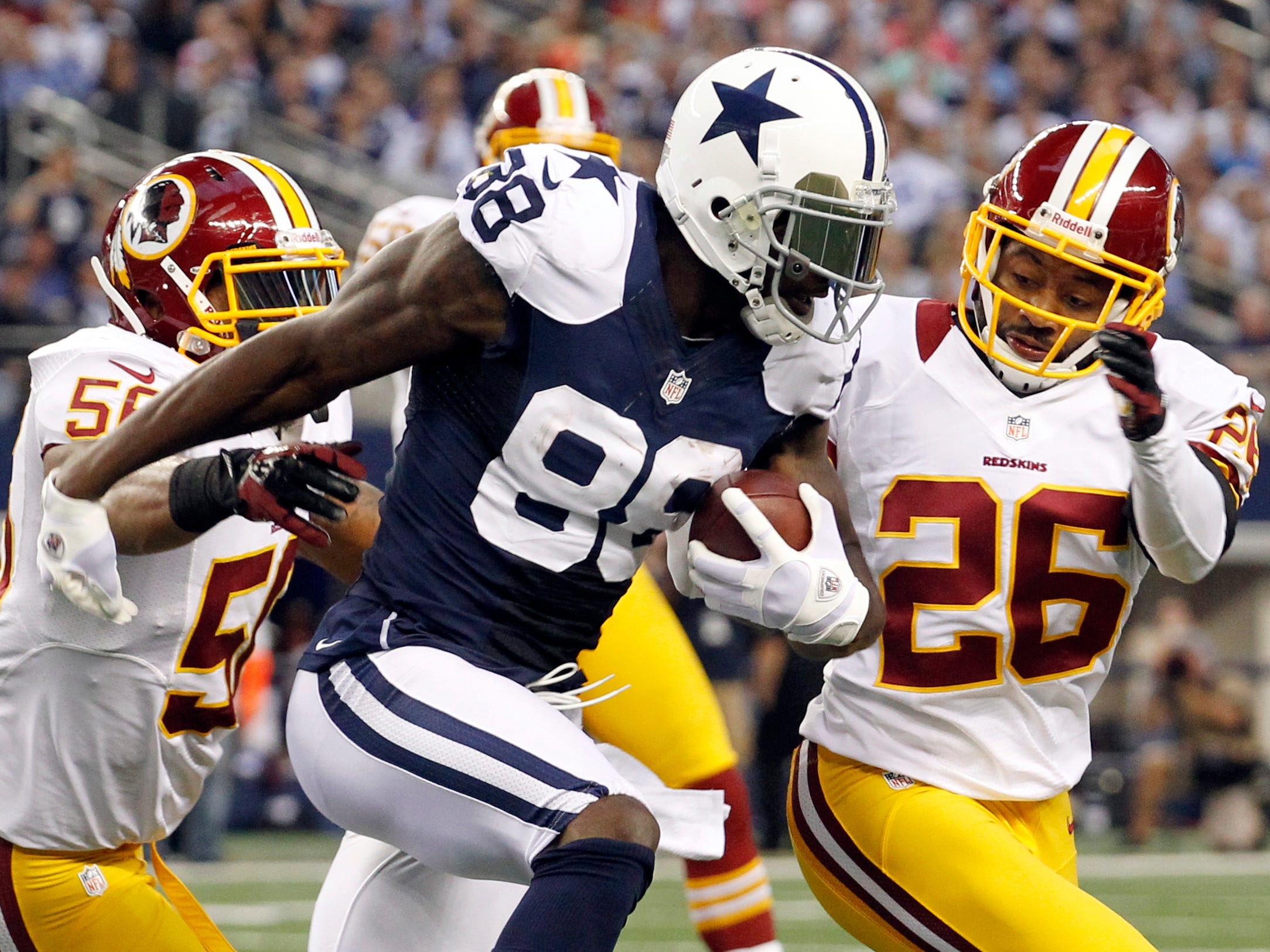 Dez Bryant is tackled by Washington Redskins' Perry Riley (56) and Josh Wilson (26) on a short run in 2012.