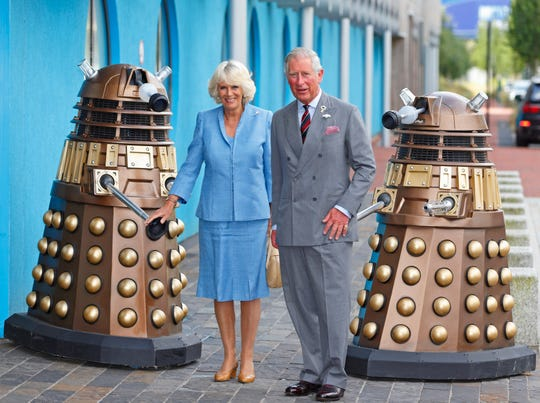 """Prince Charles and Camilla Duchess of Cornwall pose with two Daleks from """"Doctor Who"""" at BBC Roath Lock Studios on July 3, 2013 in Cardiff, Wales."""
