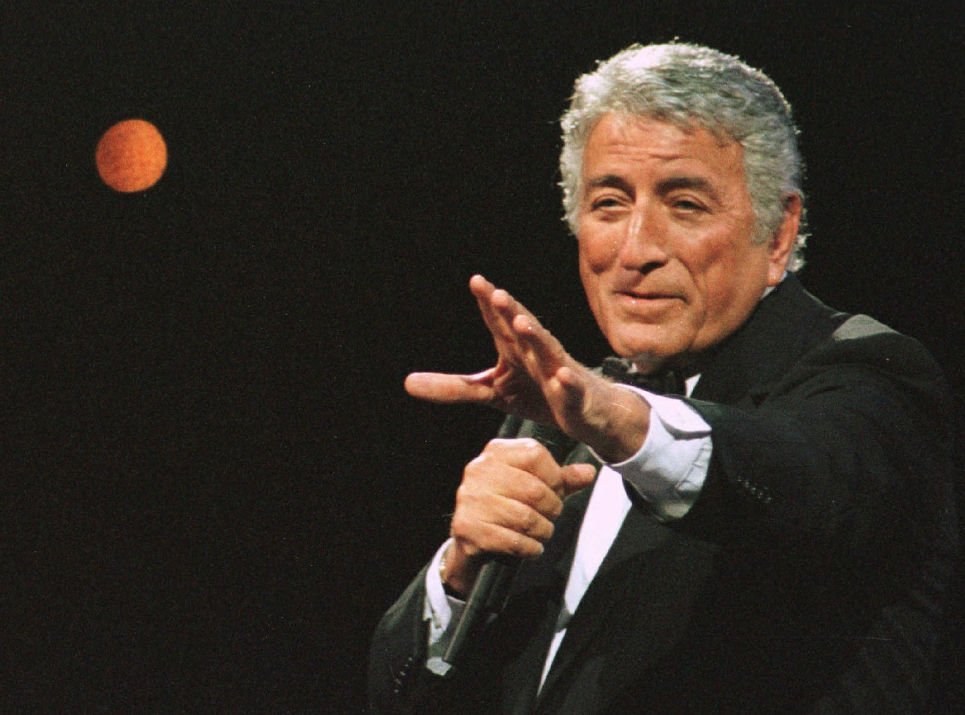 "Tony Bennett gestures during a song in his segment of "" Hear, O Israel""  at the CoreStates center in Philadelphia, Saturday, Jan. 24, 1998. ""Hear, O Israel"" was a concert event with the Israel Philharmonic and Philadelphia orchestras, inaugurating the 50th anniversary of the State of Israel in America. (AP Photo/Tim Shaffer) ORG XMIT: WILX104"