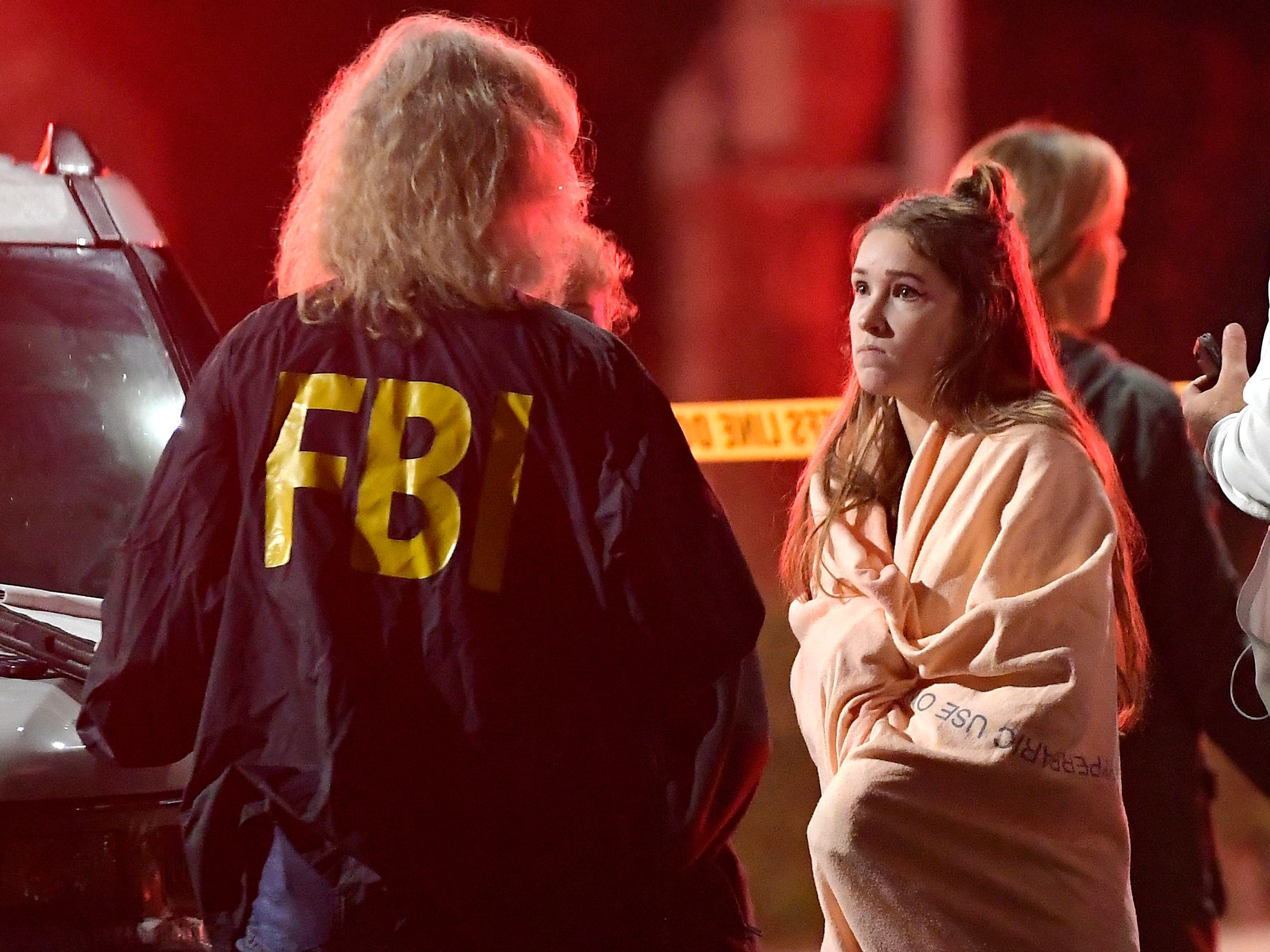 "An FBI agent talks to a potential witness as they stand near the scene Thursday, Nov. 8, 2018, in Thousand Oaks, Calif. where a gunman opened fire Wednesday inside a country dance bar crowded with hundreds of people on ""college night."""