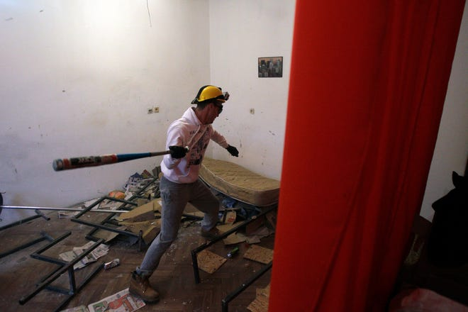 Savo Duvnjak smashes furniture and other household items during a demolishing session at the Rage Room on Dec. 27, 2012, in Novi Sad, Serbia.
