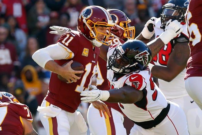Washington Redskins quarterback Alex Smith (11) is sacked by Atlanta Falcons defensive tackle Grady Jarrett (97) in the first quarter at FedEx Field.