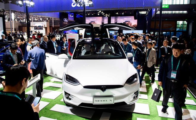 Visitors look at a Model X car of electric-carmaker Tesla Motors at the first China International Import Expo (CIIE) in Shanghai on November 6, 2018.
