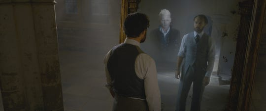 """Dumbledore (Jude Law) is haunted by visions of his old friend Grindelwald (Johnny Depp) in the Mirror of Erised in """"Fantastic Beasts: The Crimes of Grindelwald."""""""