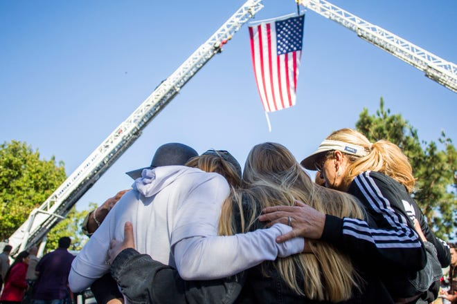 Friends hug outside Los Robles Medical Center in Thousands Oaks, California, paying tribute to Ventura Country Sheriff's Sgt Ron Helus, killed in the shooting at the Borderline Bar in Thousands Oaks on November 08, 2018. - The gunman who killed 12 people in a crowded California country music bar.