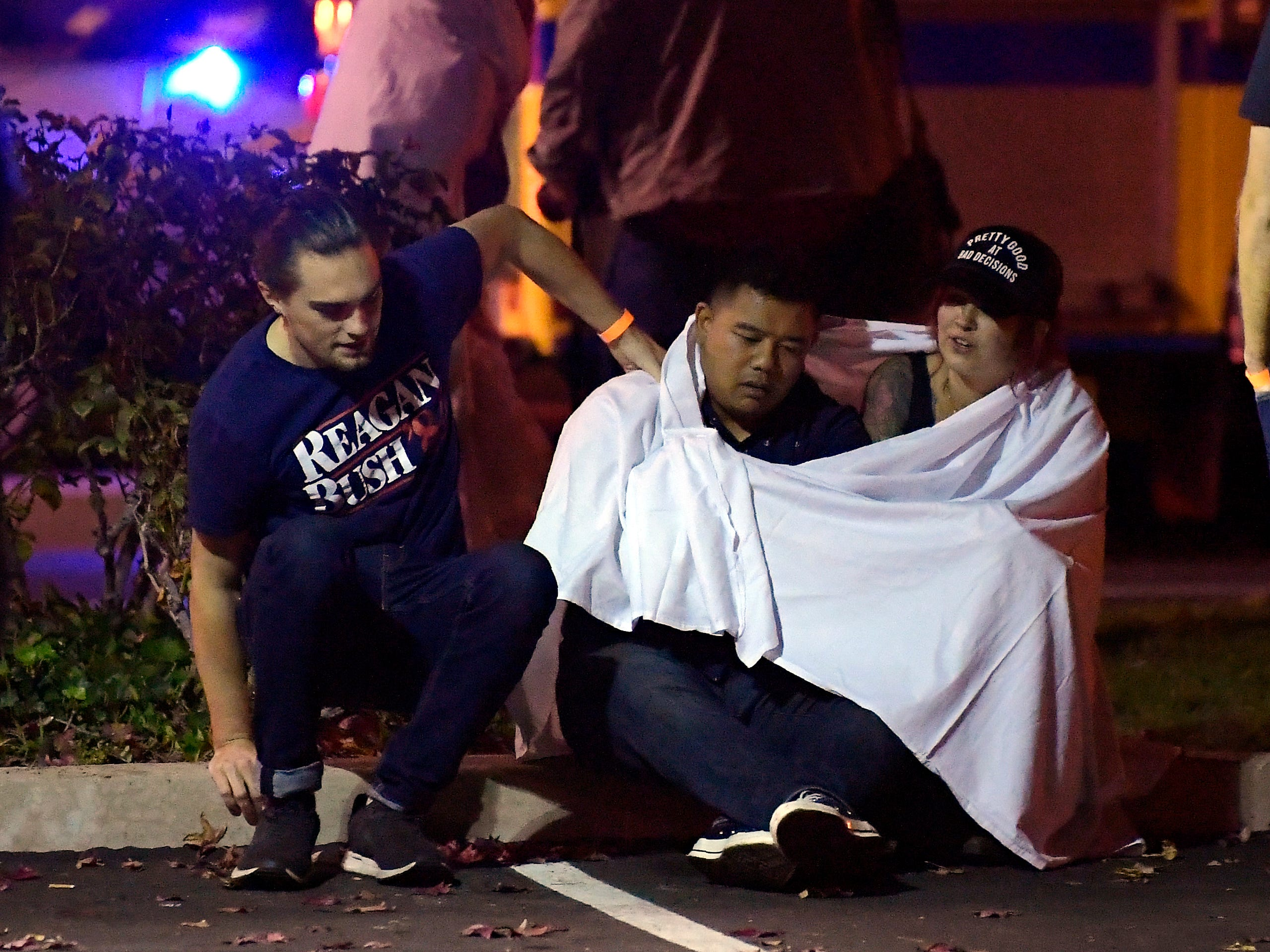 "People comfort each other at the scene in Thousand Oaks, Calif. where a gunman opened fire inside a country dance bar crowded with hundreds of people on ""college night,"" on Nov. 8, 2018."