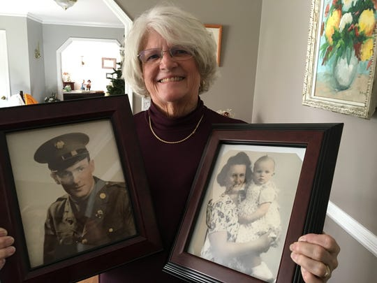 Carol Donahue holding portraits of her father Stephen and mother Eleanor.