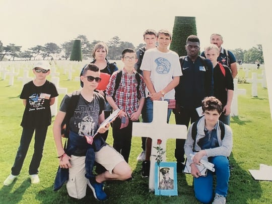 French students stand by the grave of Sgt. Stephen Coleman in Normandy.