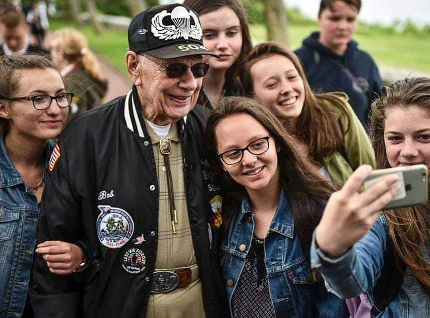 French students give a hero's welcome to American World War II veteran Bob Devinney in a meeting arranged by Valerie Gautier Cardin earlier this year.
