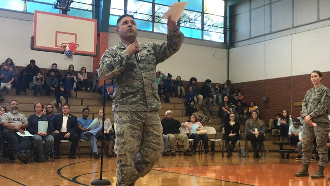 Air Force Tech Sgt. Hugo Bernal addresses Madison Middle School's Veterans Day celebration crowd Friday. Bernal, whose wife, Marissa Bernal, teaches sixth-grade English at the school, advised the students about the importance of Veterans Day with the Air Force's Esther Spaulding, right.