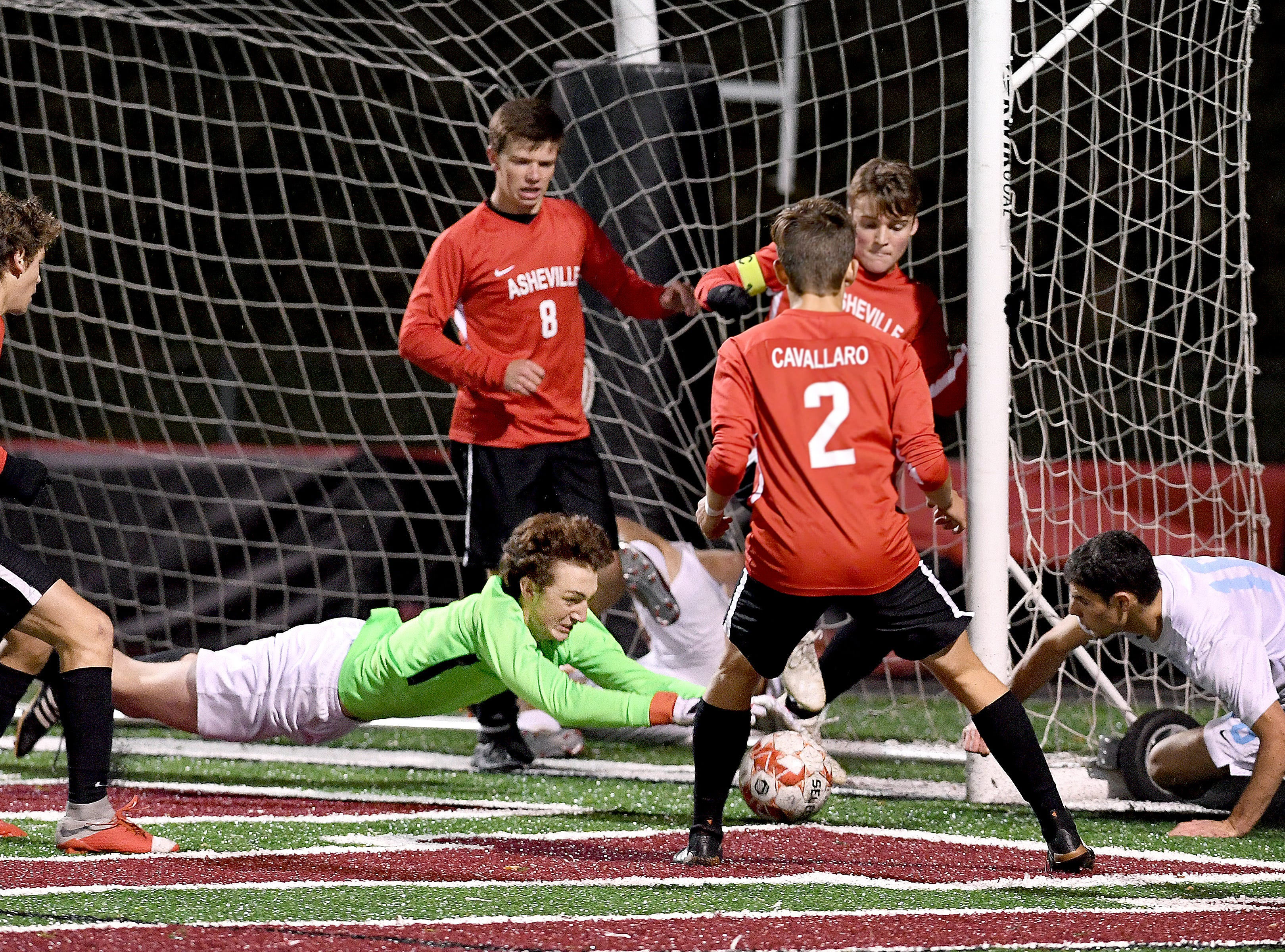 Asheville goalie Max Butterworth leaps onto the ball  during the Cougars' playoff game against Watauga at Asheville High School on Nov. 8, 2018. The Cougars defeated the Pioneers 1-0 to advance.