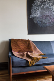 One of Amber Jensen's large scale drawings hung behind a couch with one of her handmade textiles draped over the end.