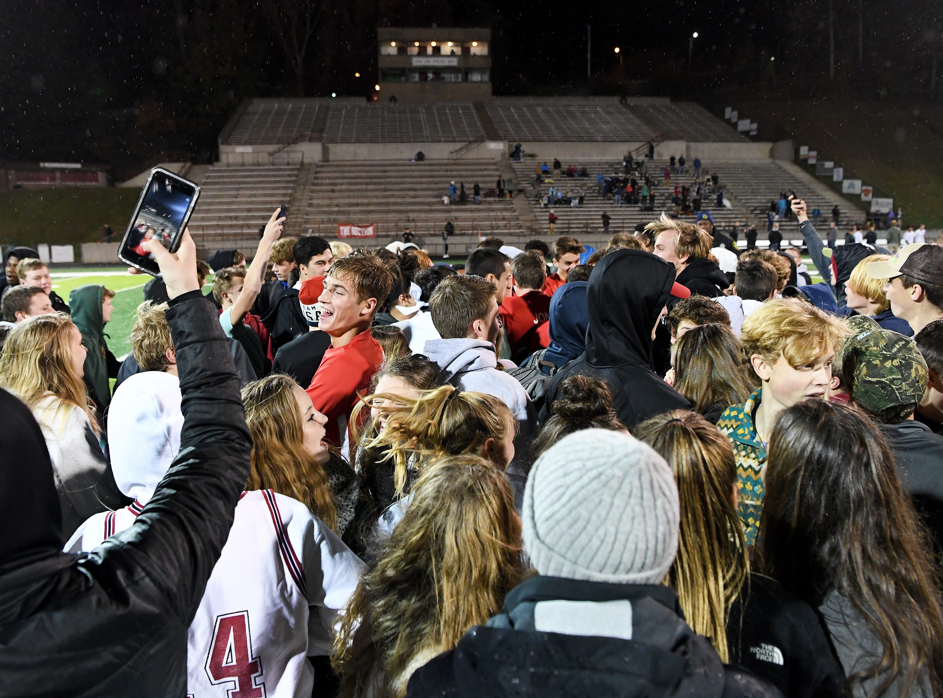Asheville's Justin Fleer jumps up and down with the student section after they rushed the field to celebrate the Cougars' 1-0 playoff win over Watauga to advance at Asheville High School on Nov. 8, 2018.