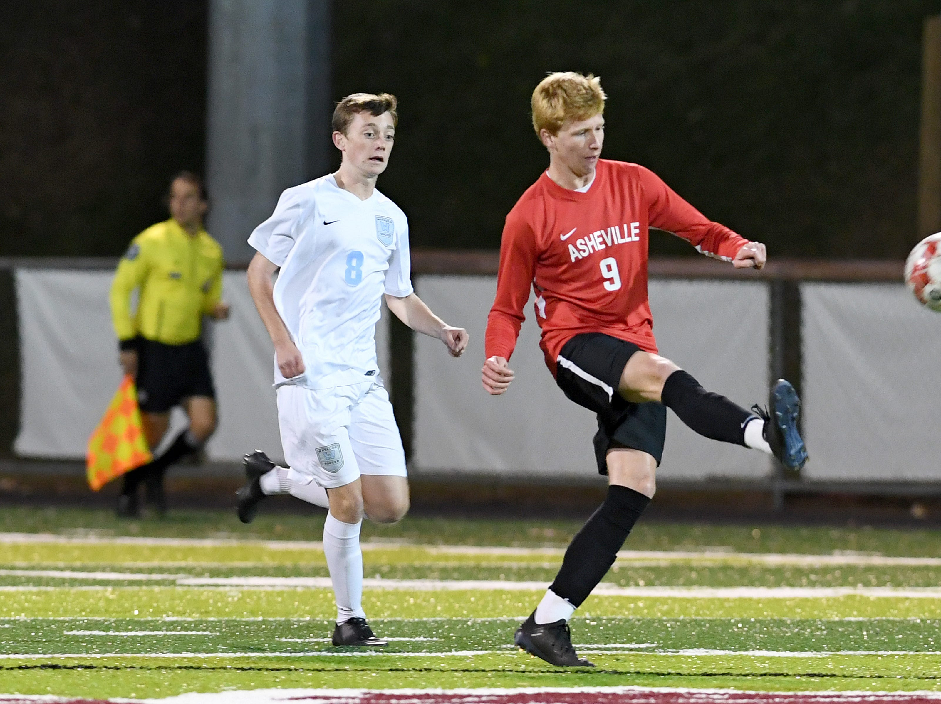 Asheville's Michael Wilkerson reaches the ball ahead of Watauga's Jake Ganley during their playoff game at Asheville High School on Nov. 8, 2018. The Cougars defeated the Pioneers 1-0 to advance.