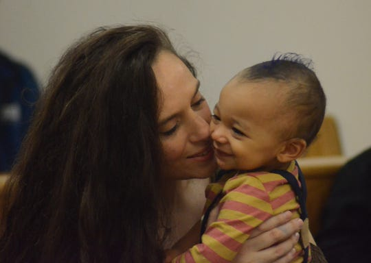 Stephanie Clay kisses her newly adopted son, Maddox on Friday.