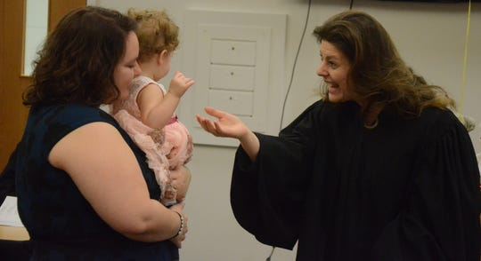 Circuit Court Judge Tina Yost Johnson greets Annaleesia Gibson, held by her mother, BreAnna Gibson.