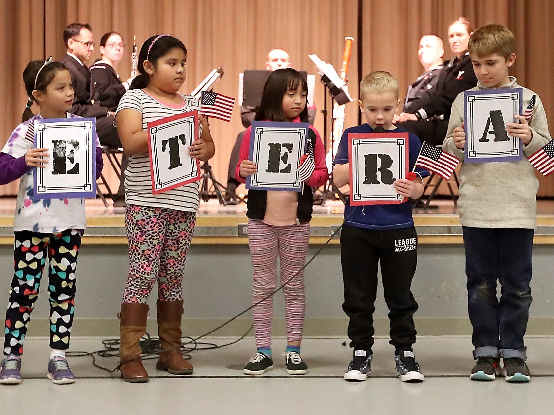 "Students in Ann Kim's second grade class spell out VETERAN with signs as they present their tribute ""What is a Veteran?"" during the Veterans Day Celebration at PineCrest Elementary School in Bremerton on Friday, November 9, 2018."
