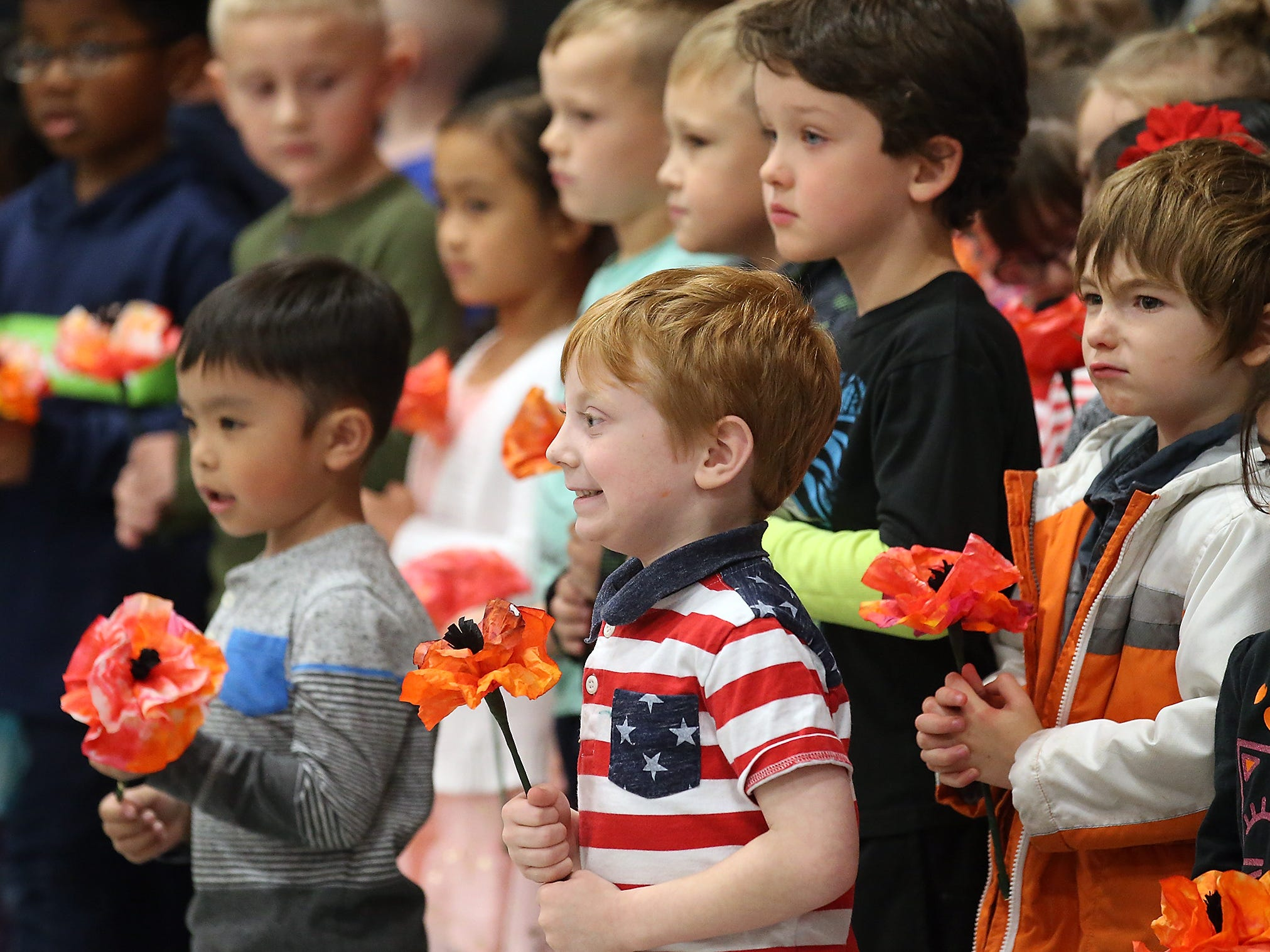 "While wearing a patriotic shirt, kindergartner Levi Poore smiles at the crowd during his class' singing of ""The Veteran Song"" during the Veterans Day Celebration at PineCrest Elementary School in Bremerton on Friday, November 9, 2018."
