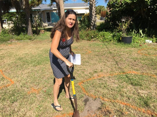 Sandra Sullivan digs in her back yard Thursday, where she's been finding pieces of metal and other items she suspects are old military waste from the World War II era.