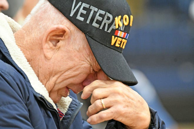 Clayton Ray Clark is overcome with emotion Friday morning as the Galion Marching Band plays the Marines' Hymn during a program to honor veterans. Clark, who left Galion High School in 1952 to serve with the US Marine Corps in Korea, received his diploma.