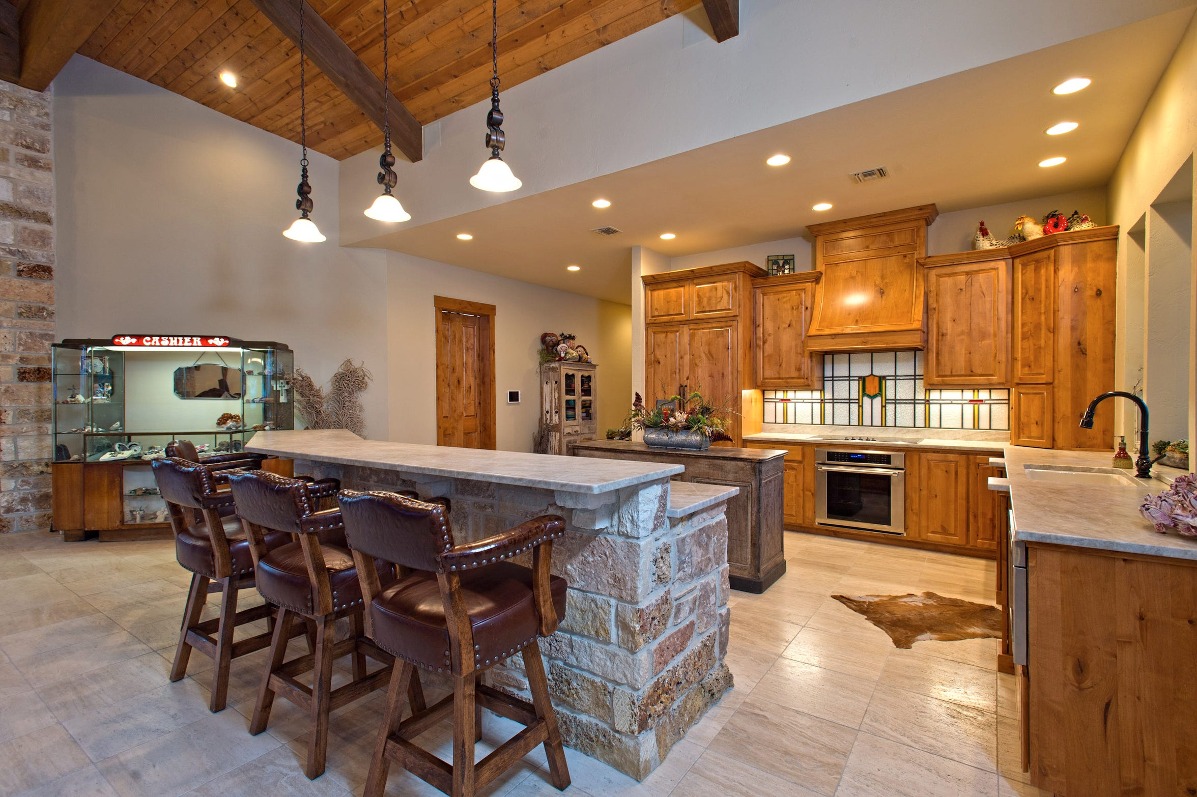 A unique stained glass backsplash, a rock breakfast bar and an antique cashier station purchased  from a local restaurant auction are highlights of the open concept kitchen