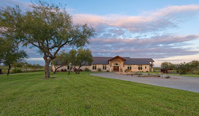 The Texas Hill Country stye home, crafted with stone and a metal roof   was built on the highest point of elevation allowing breathtaking views of the entire ranch and wildlife.