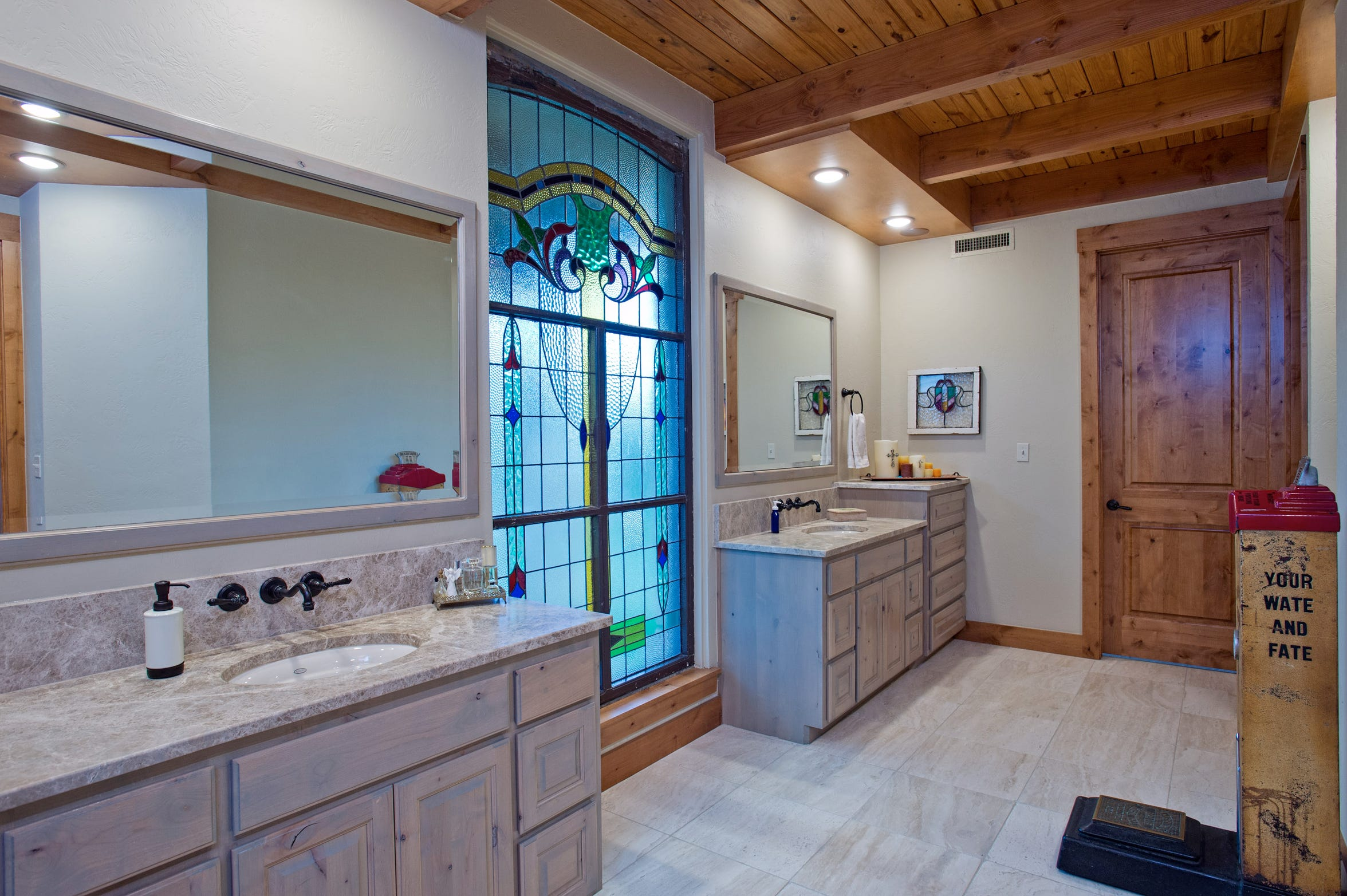 A large stained glass window lets the perfect light into the master bath area